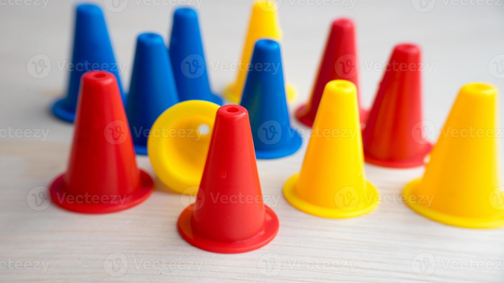 Multiple colour mini plastic safety cones on wooden surface photo