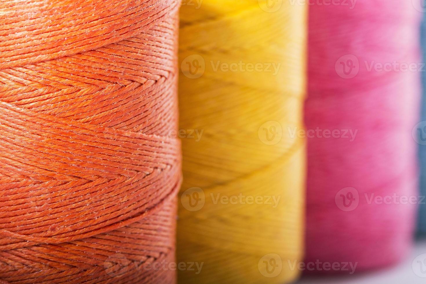 carretes de hilo en amarillo, naranja y rosa foto