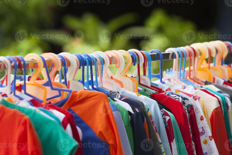 Clothes hang on a shelf photo