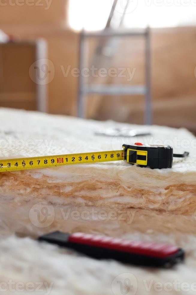 cinta métrica y cuchillo sobre lana mineral foto