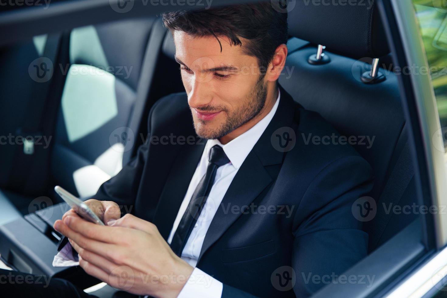 Businessman using smartphone in car photo