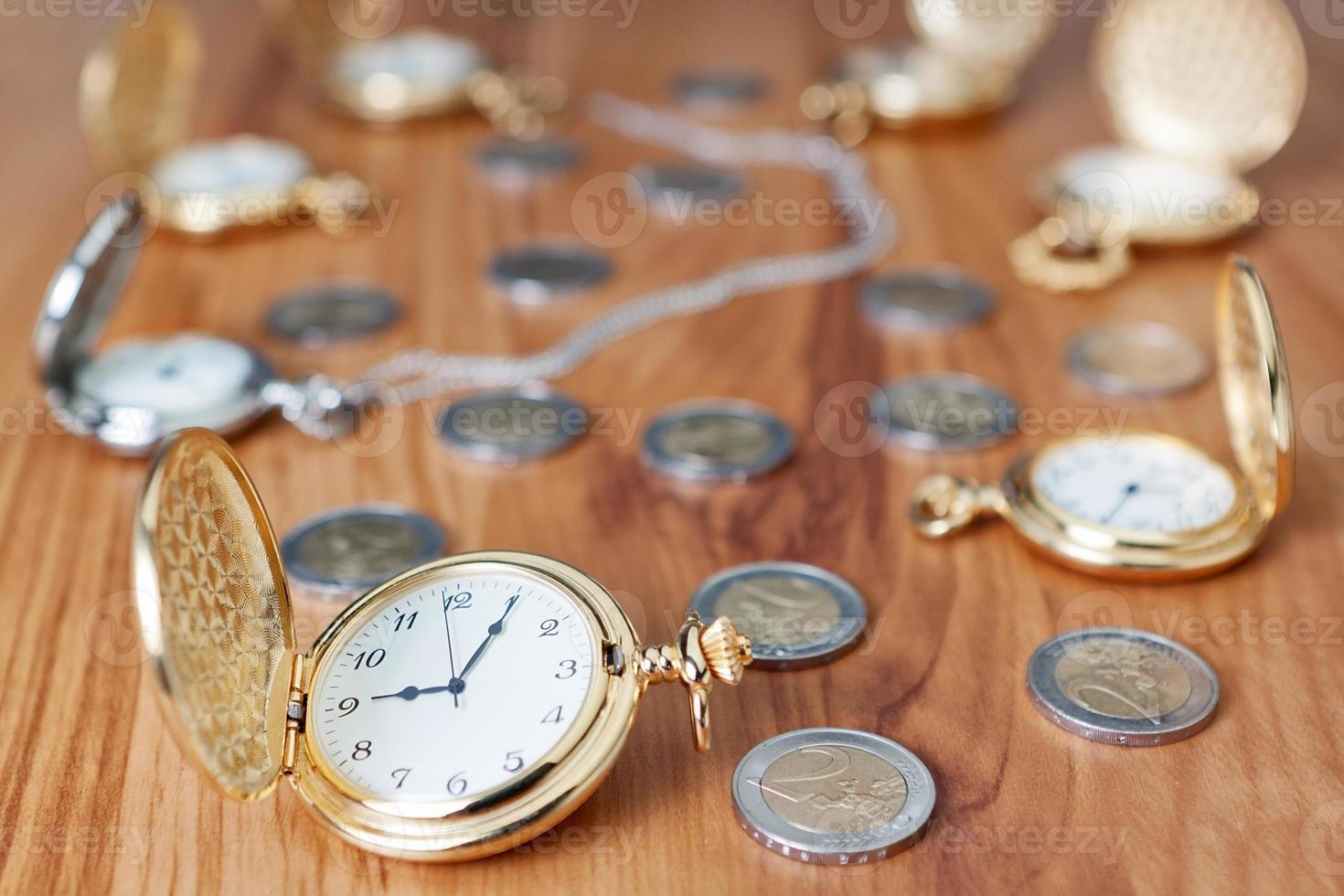 Group gold pocket watch against the euro coins. photo