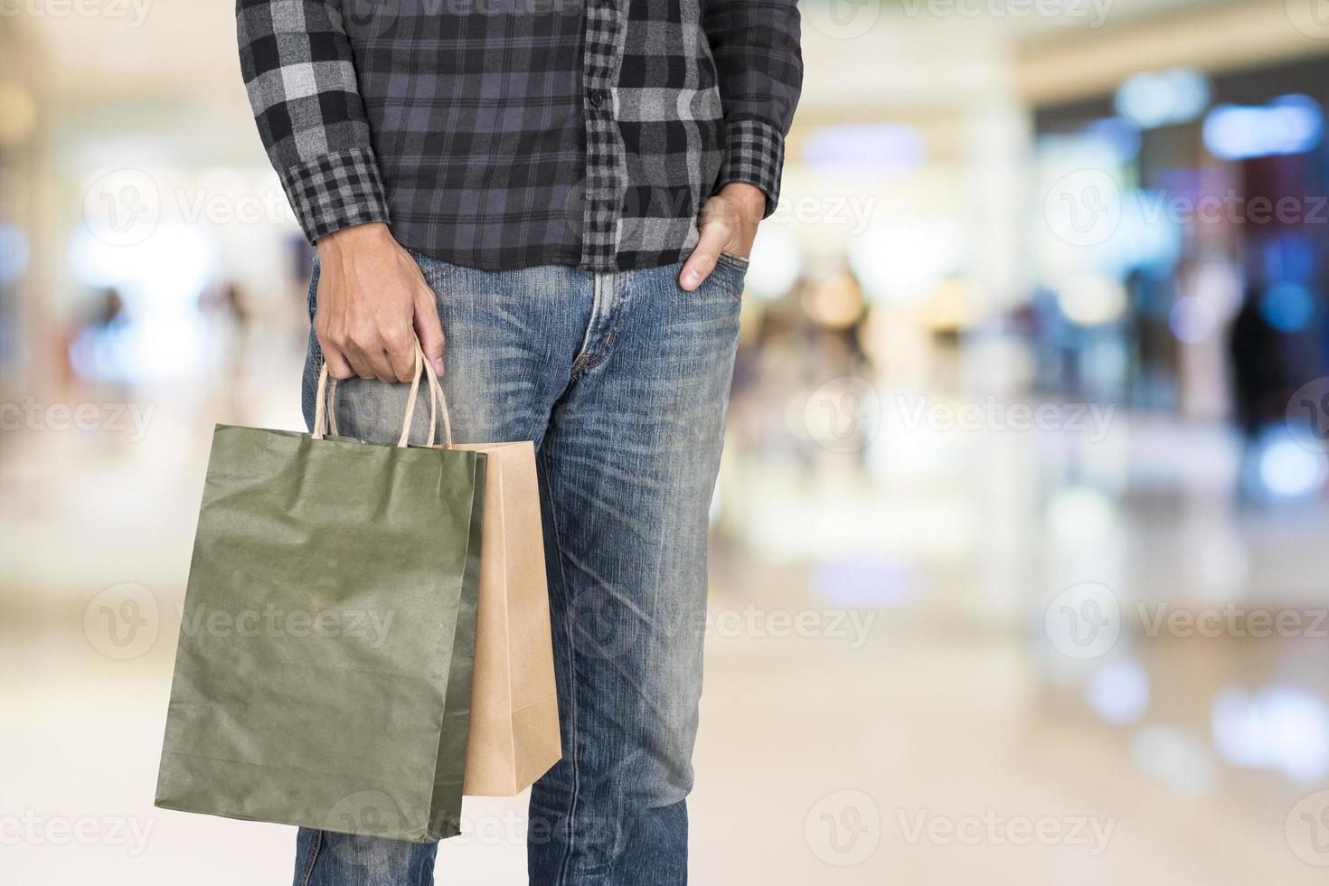 Exciting young shopping man hold bags, closeup portrait with copyspace. photo