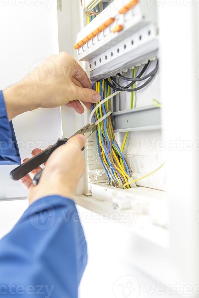 electricista revisando el cableado en una caja de fusibles foto