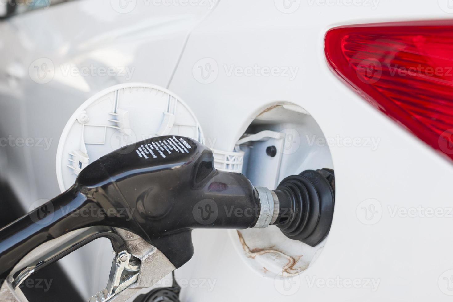 rellenar el tanque del automóvil en la estación de combustible foto