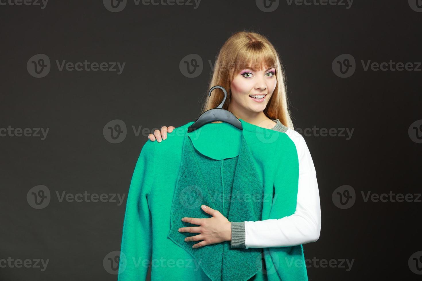 Fashionable woman holding green coat photo