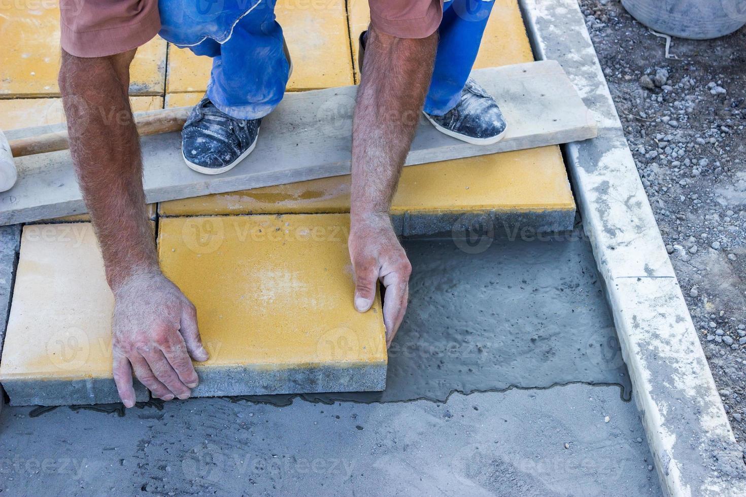 worker puts concrete pavers 3 photo