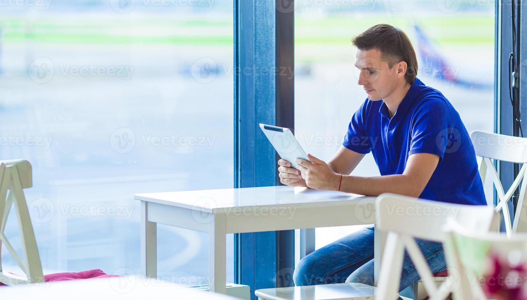 joven en la cafetería del aeropuerto mientras espera el embarque foto