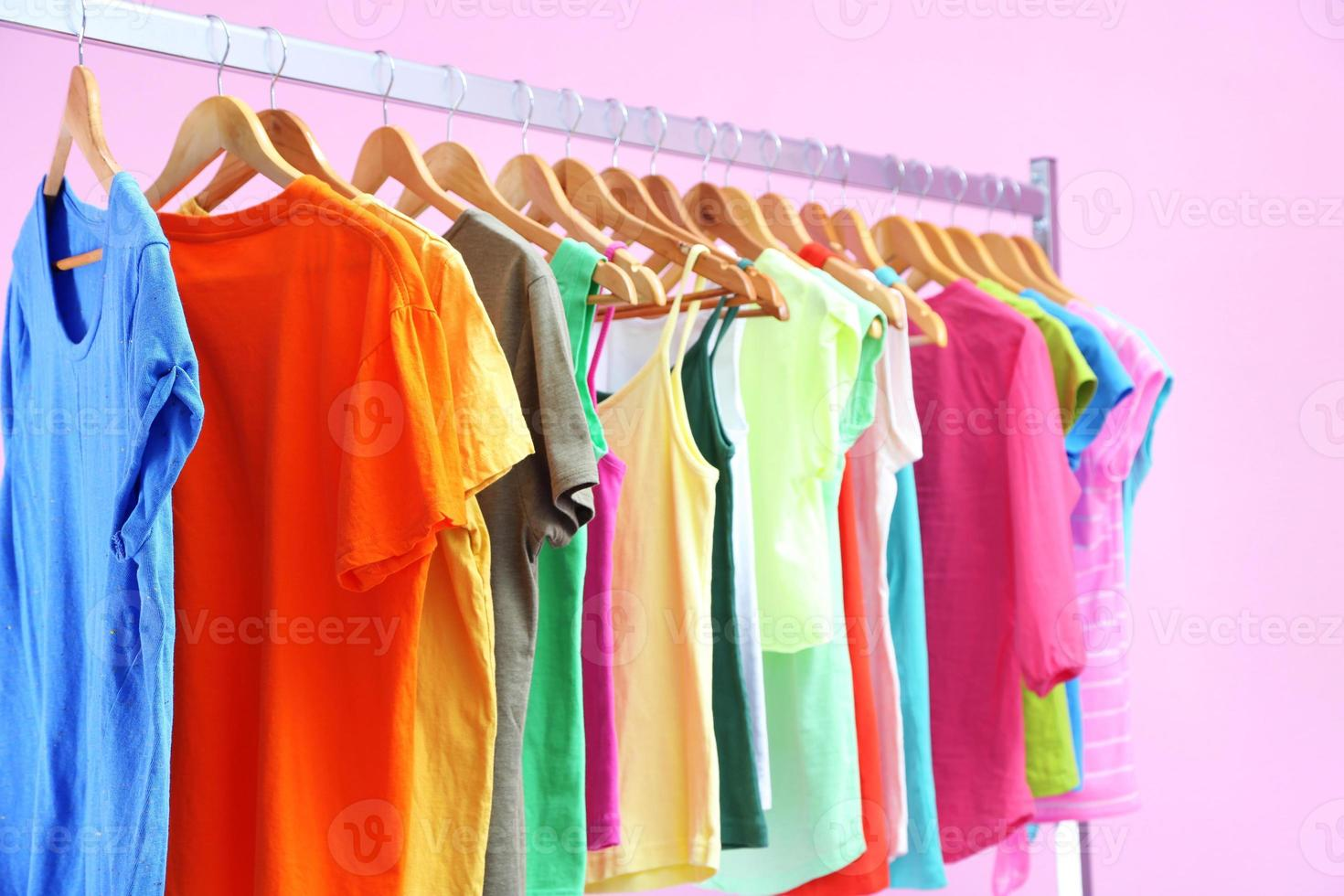Different clothes on hangers, on pink background photo