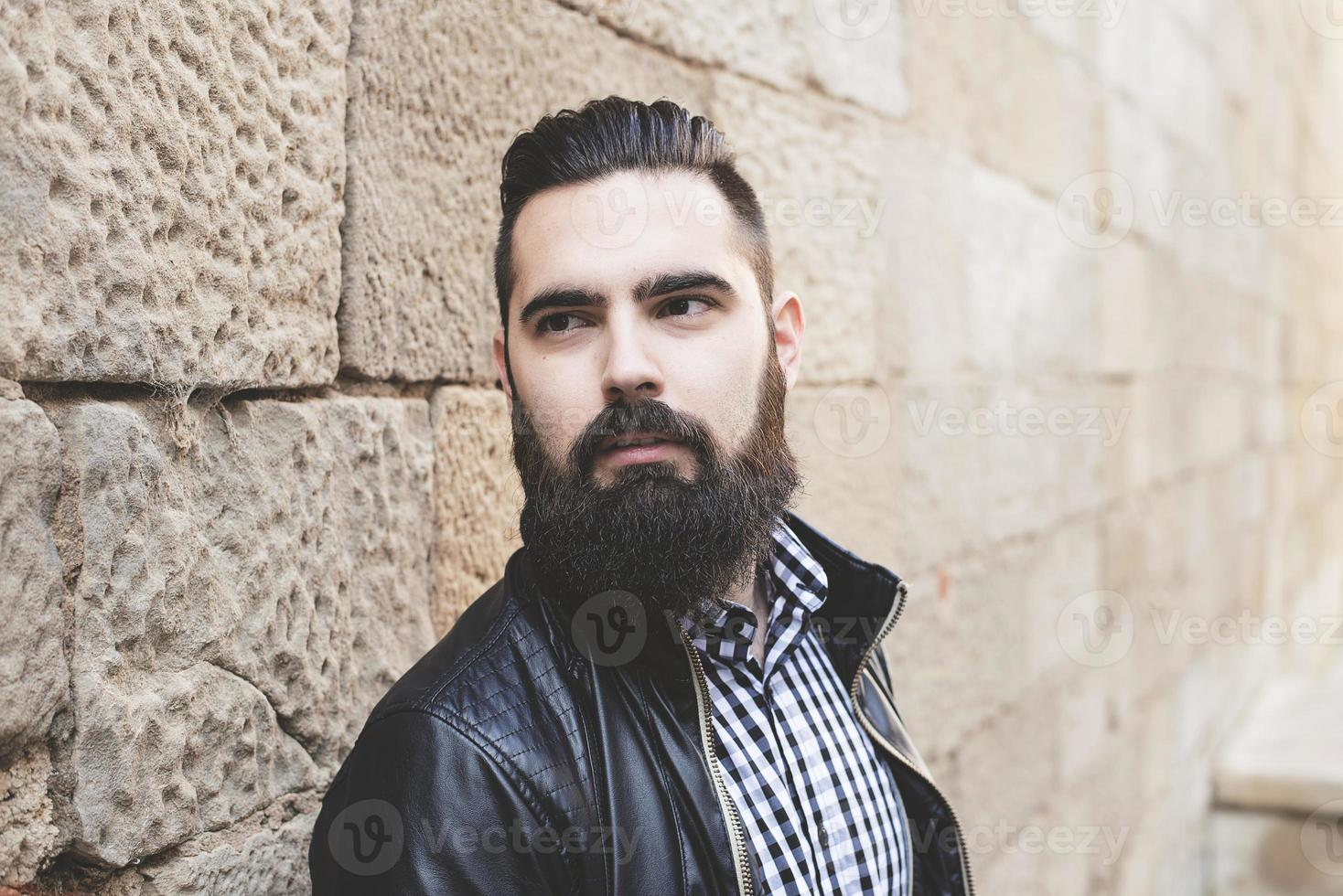 Closeup of modern young bearded man leaning against the wall. photo