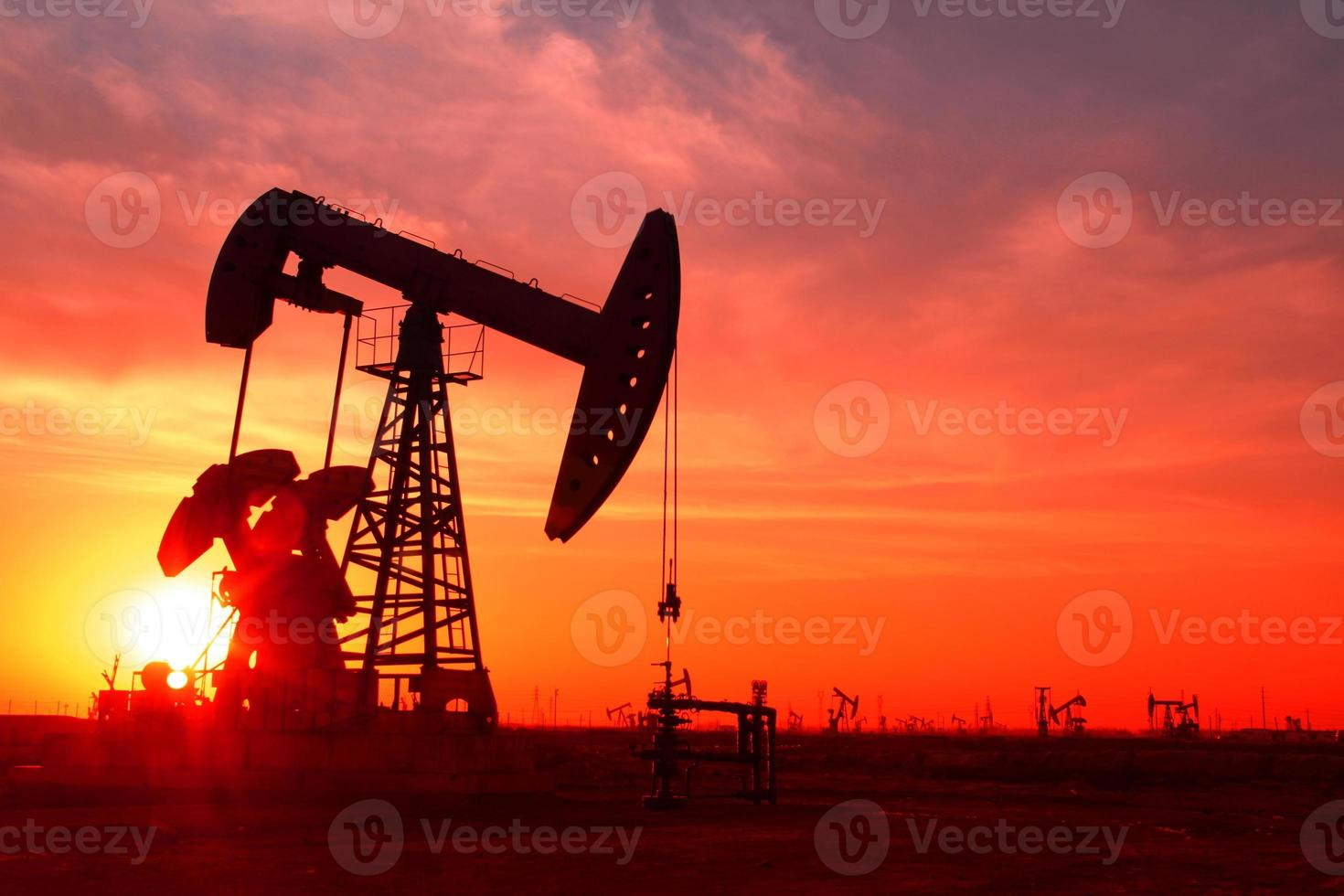 A silhouette of an oil pump in an oil field at sunset photo