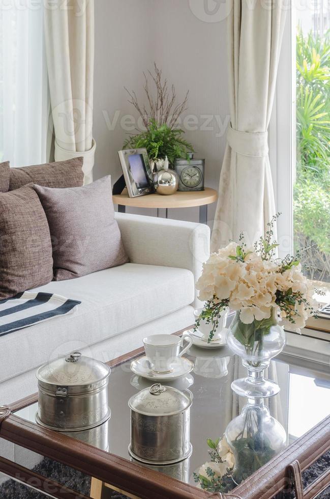 Flor en florero de cristal sobre la mesa en la sala de estar foto