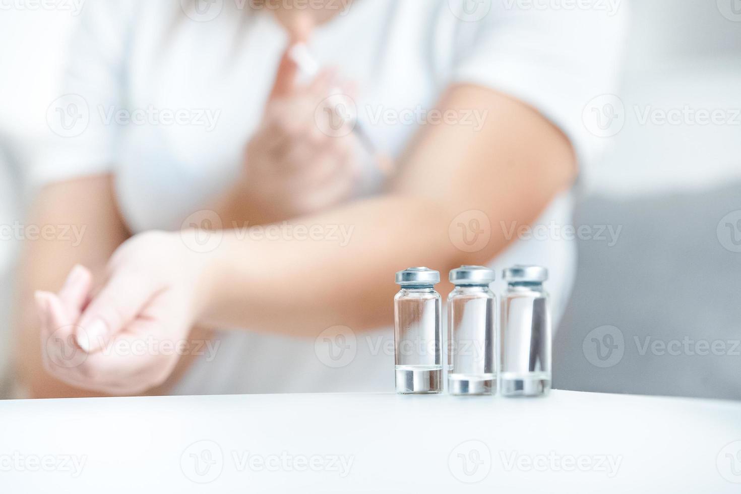 frascos de vidrio con insulina contra mujer haciendo pinchazo foto