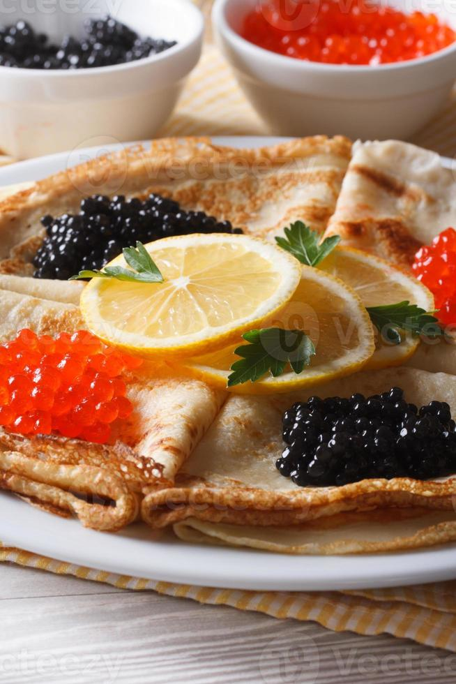 Thin pancakes with red and black caviar close-up, vertical photo