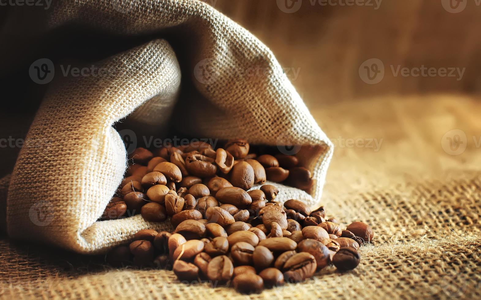 granos de café tostado se derraman de la bolsa foto