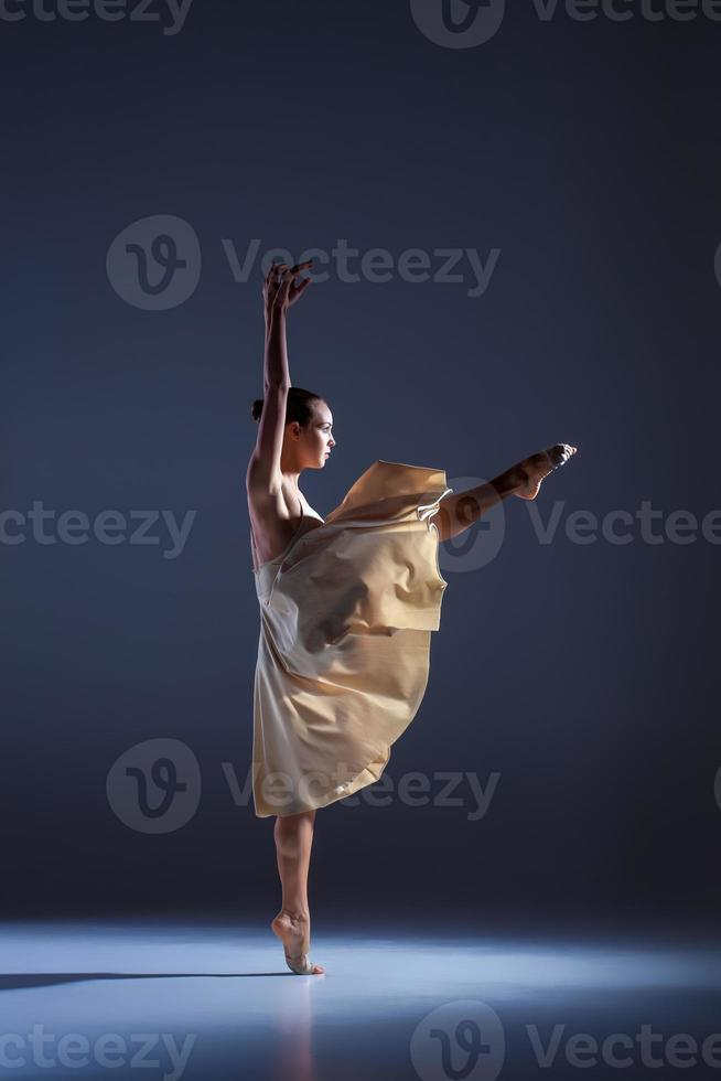 Joven bailarina hermosa en vestido beige bailando sobre fondo gris foto