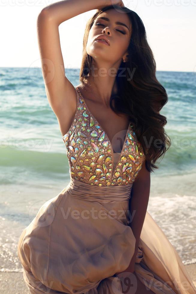 Chica con cabello oscuro en lujoso vestido posando en la playa foto
