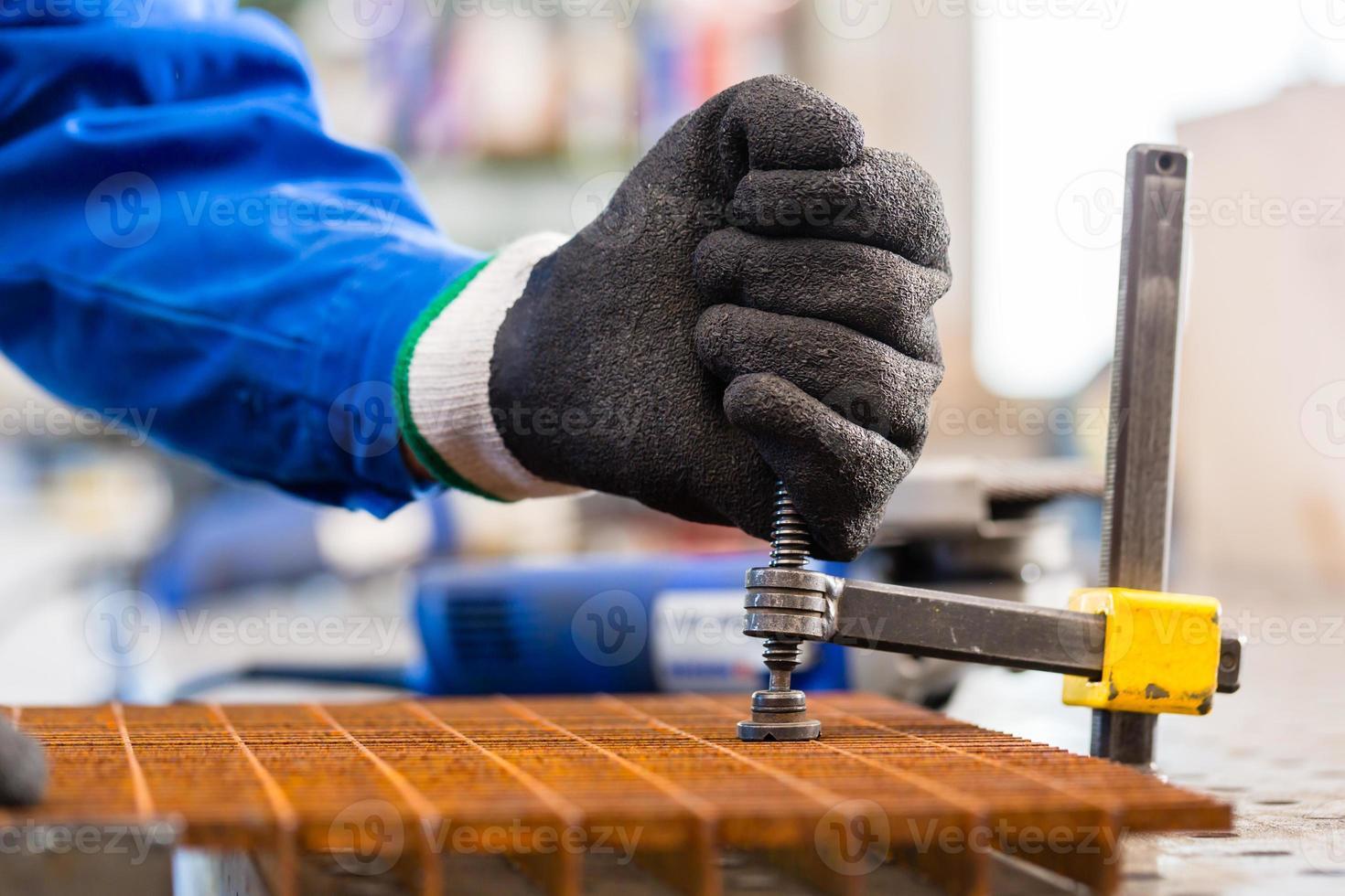 Workshop craftsman clamping metal on workbench photo