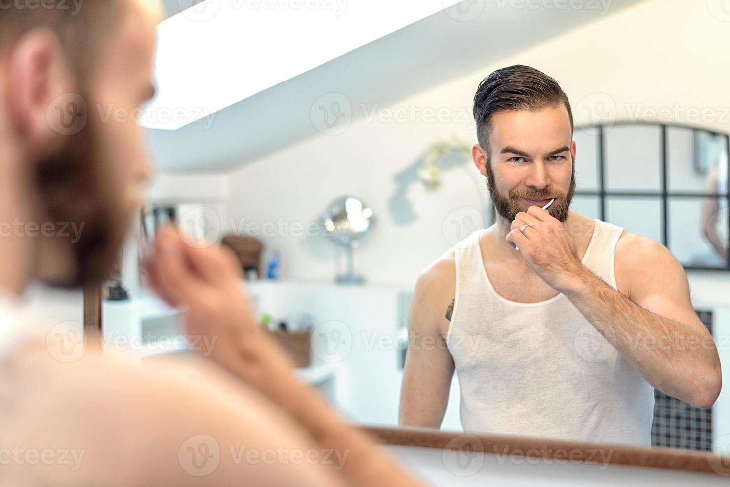 hombre barbudo que se cepilla los dientes foto