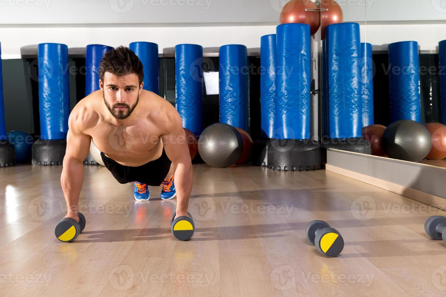 Dumbbells push-ups man at fitness gym photo