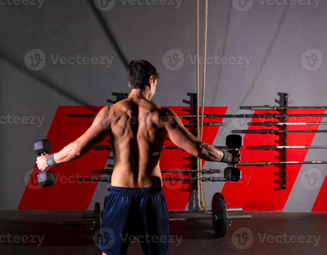 hex dumbbells man workout rear view at gym photo