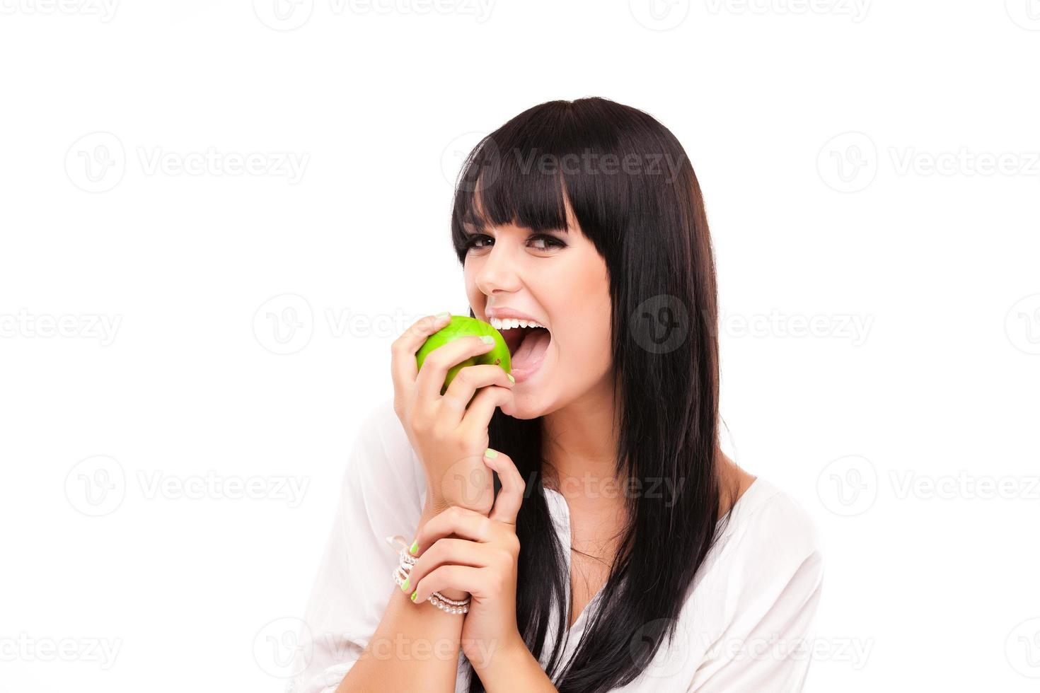 beautiful brunette woman with green apple on white background photo