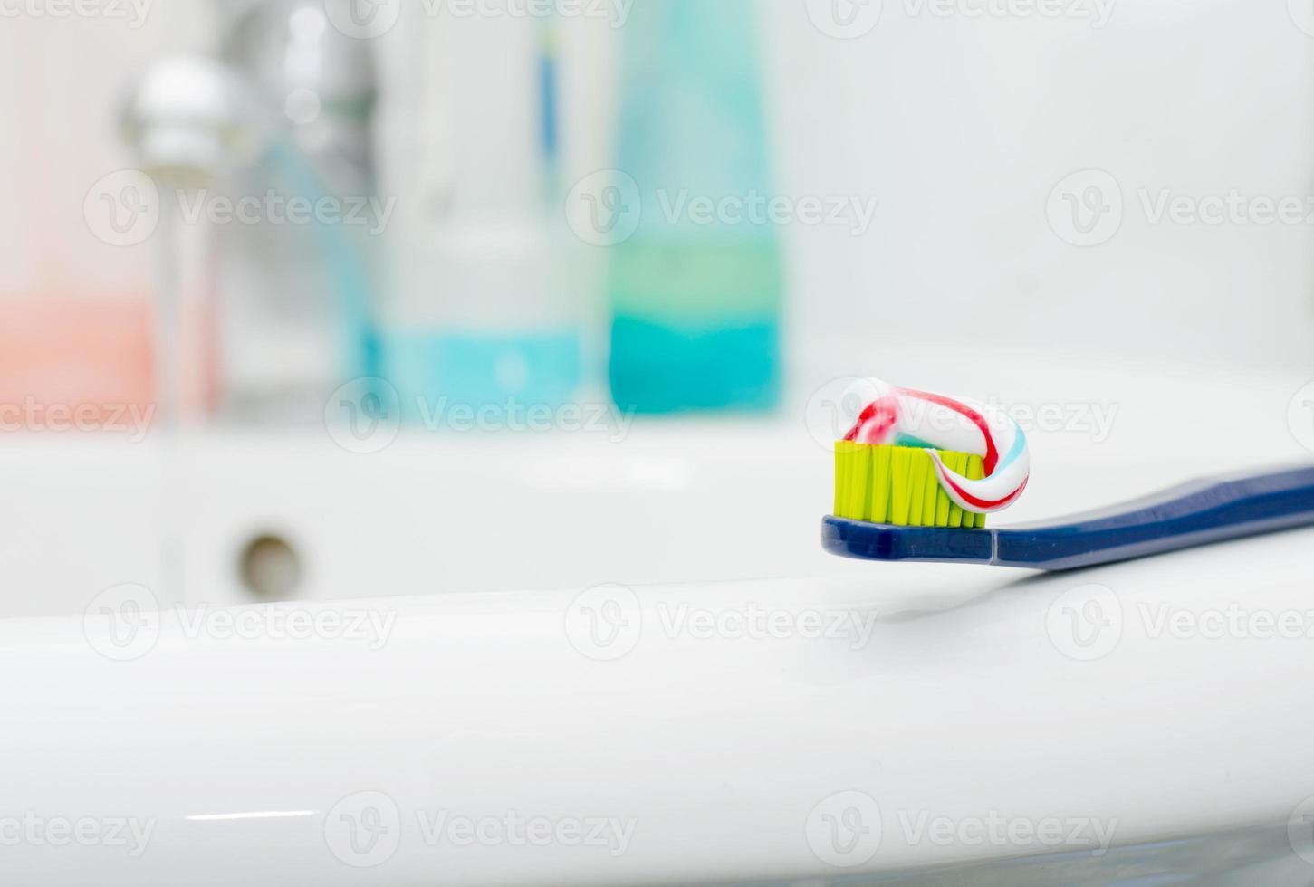 cepillo de dientes con pasta dental en el fregadero foto