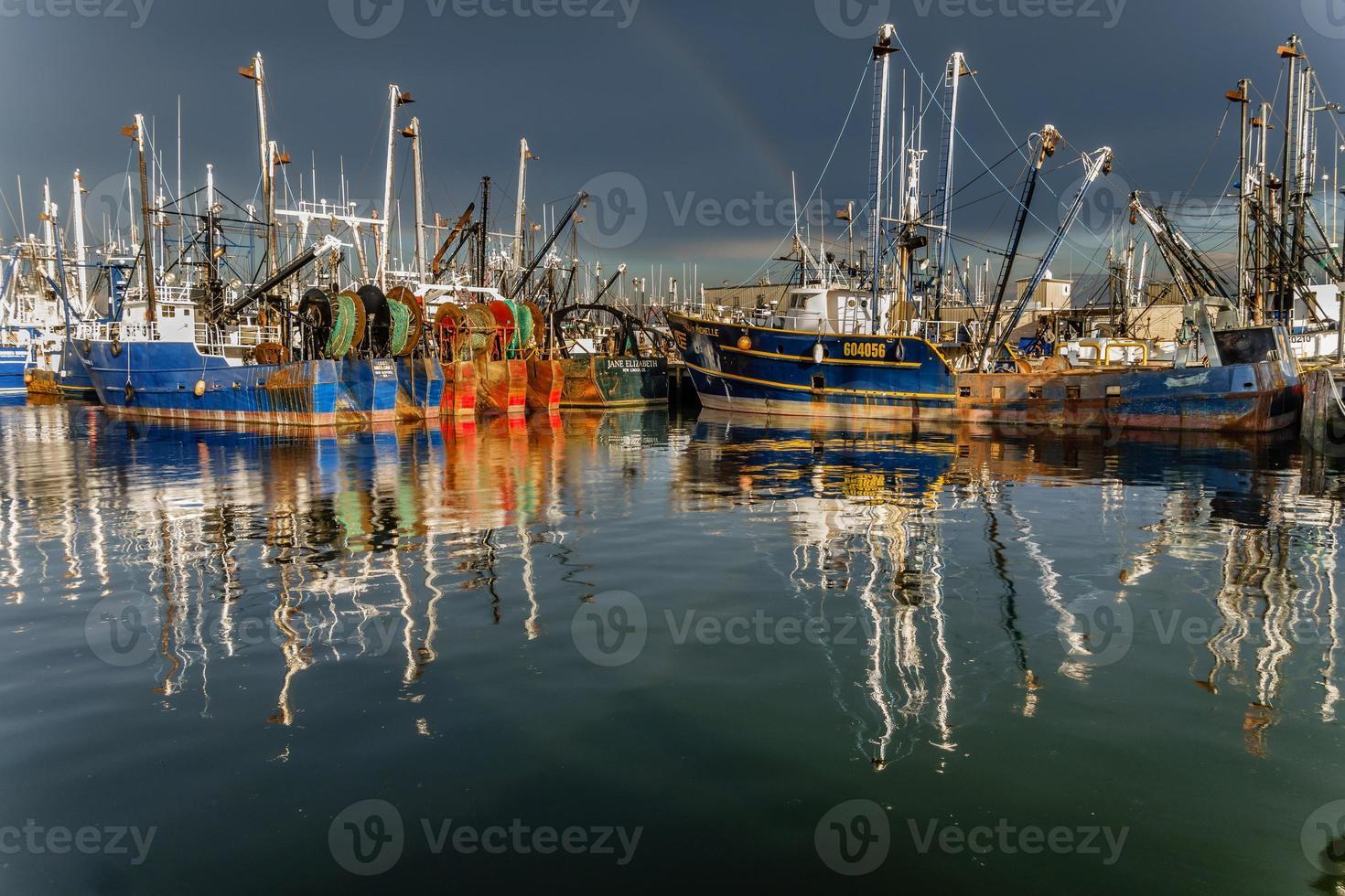 Barcos de pesca después de la tormenta con arco iris foto