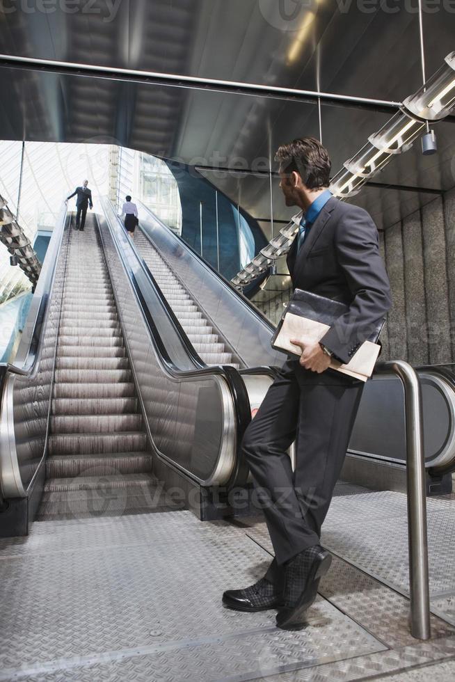Germany, Bavaria, Munich, businessman at subway station waiting by escalator photo