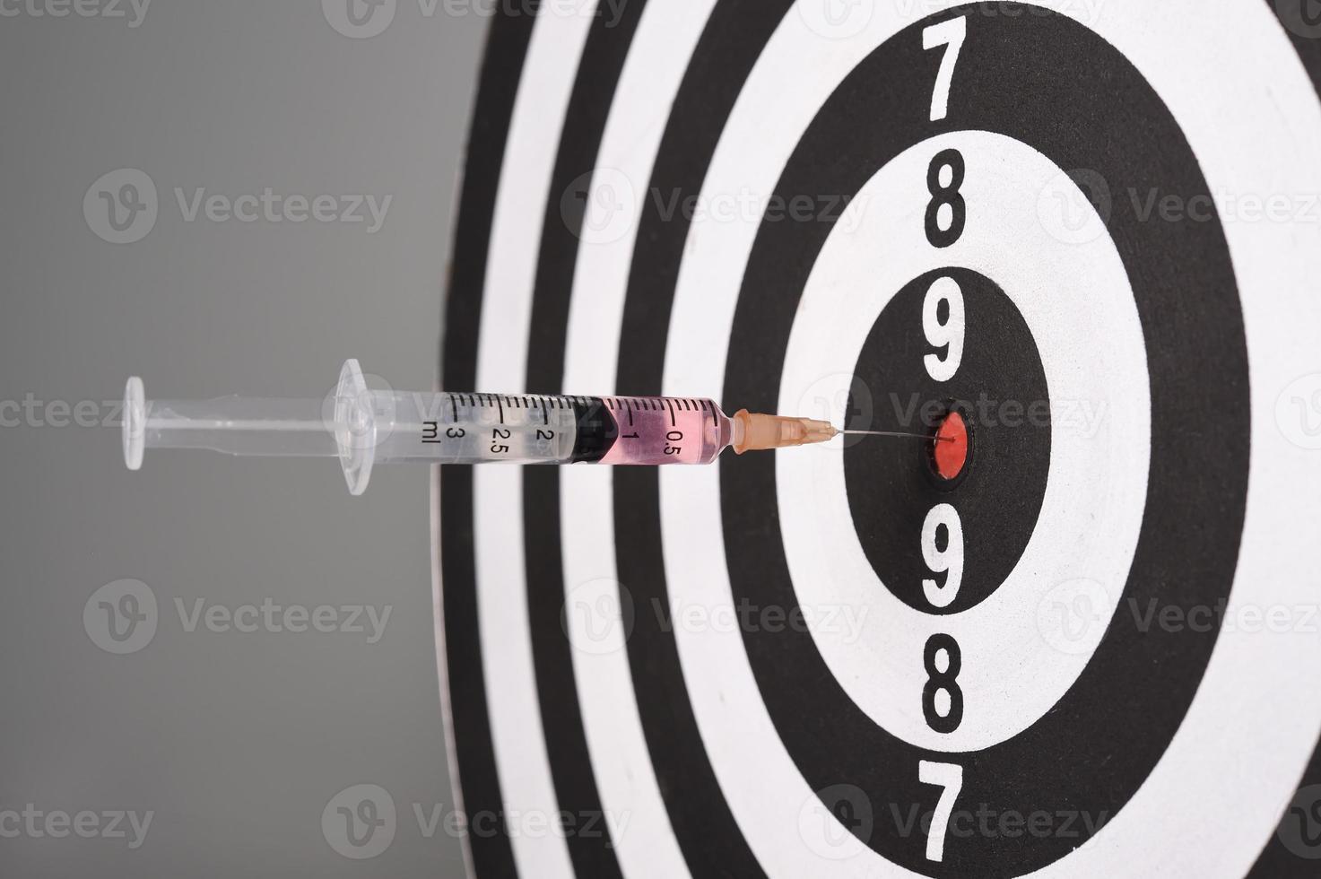 Syringe in dart board photo