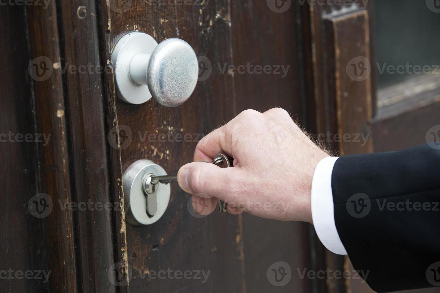 primer plano de la mano con llave en una puerta foto