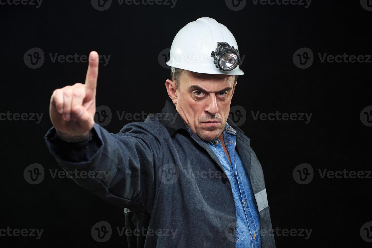 hombre con sombrero de minero de carbón y ropa de seguridad señala con el dedo foto