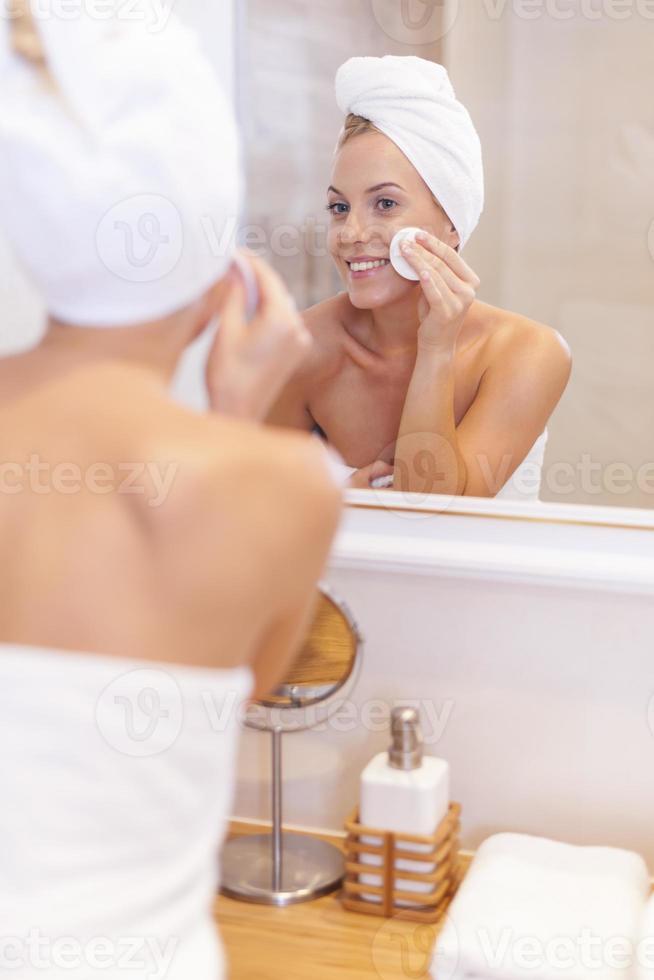 mujer limpiando la cara delante del espejo foto