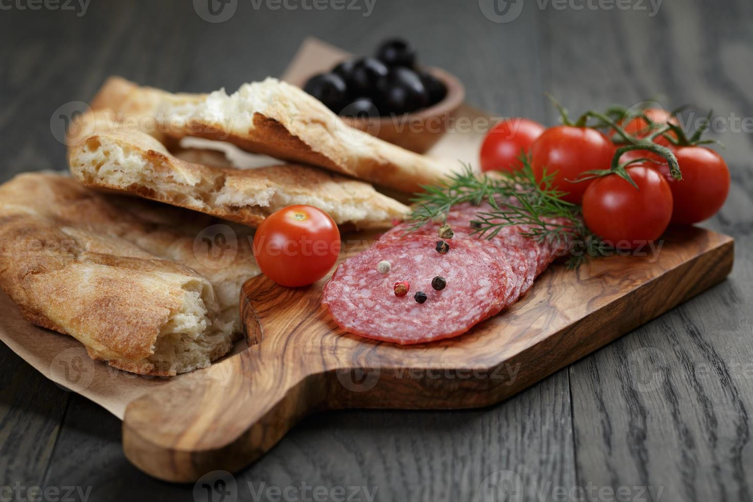 Antipasti with salami, olives, tomatoes and bread photo