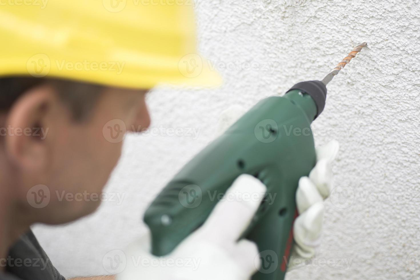 Construction worker using electric drill on concrete wall photo