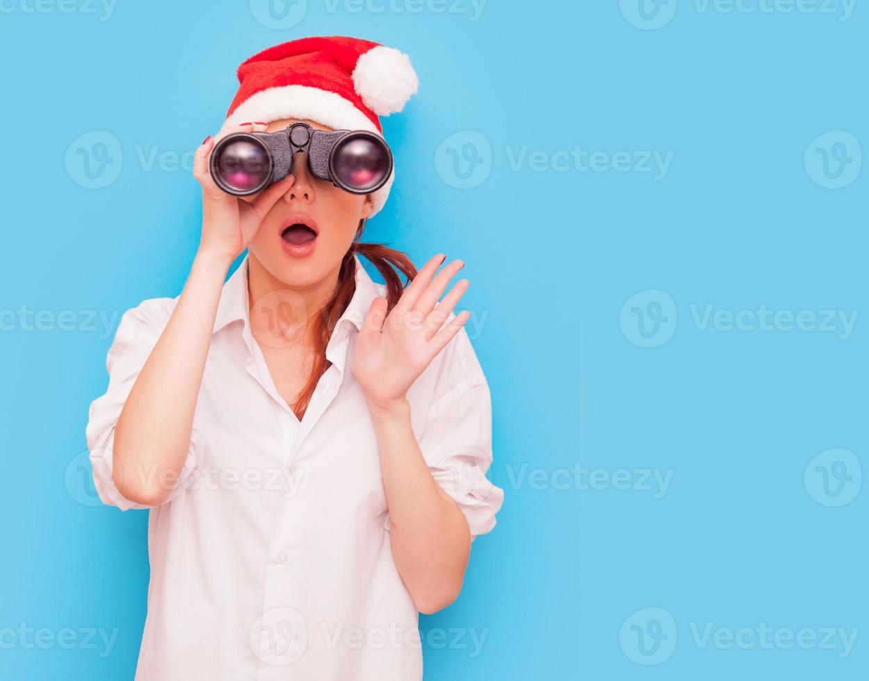 mujer con binoculares sobre fondo azul foto