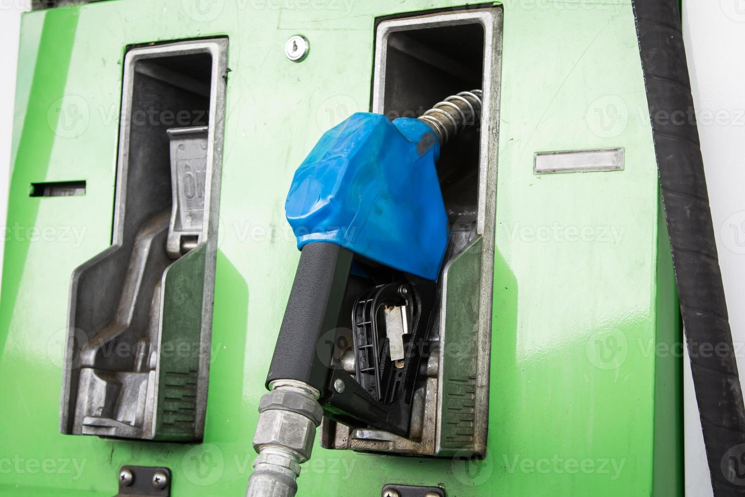 Gas pump nozzles in service station photo