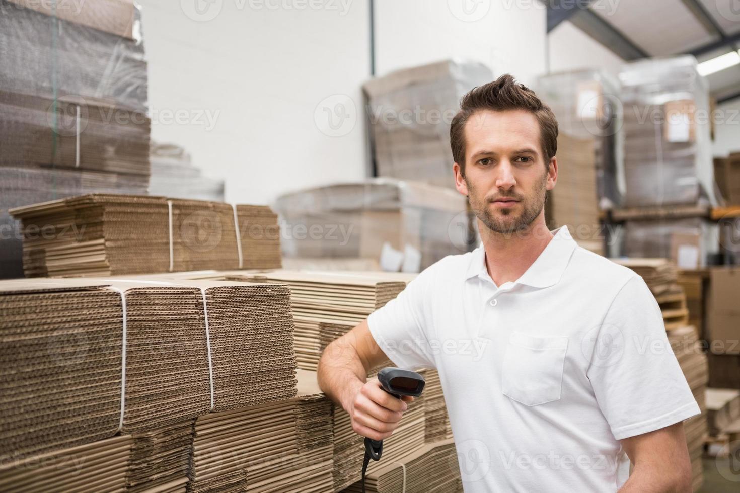 trabajador de almacén serio con escáner foto