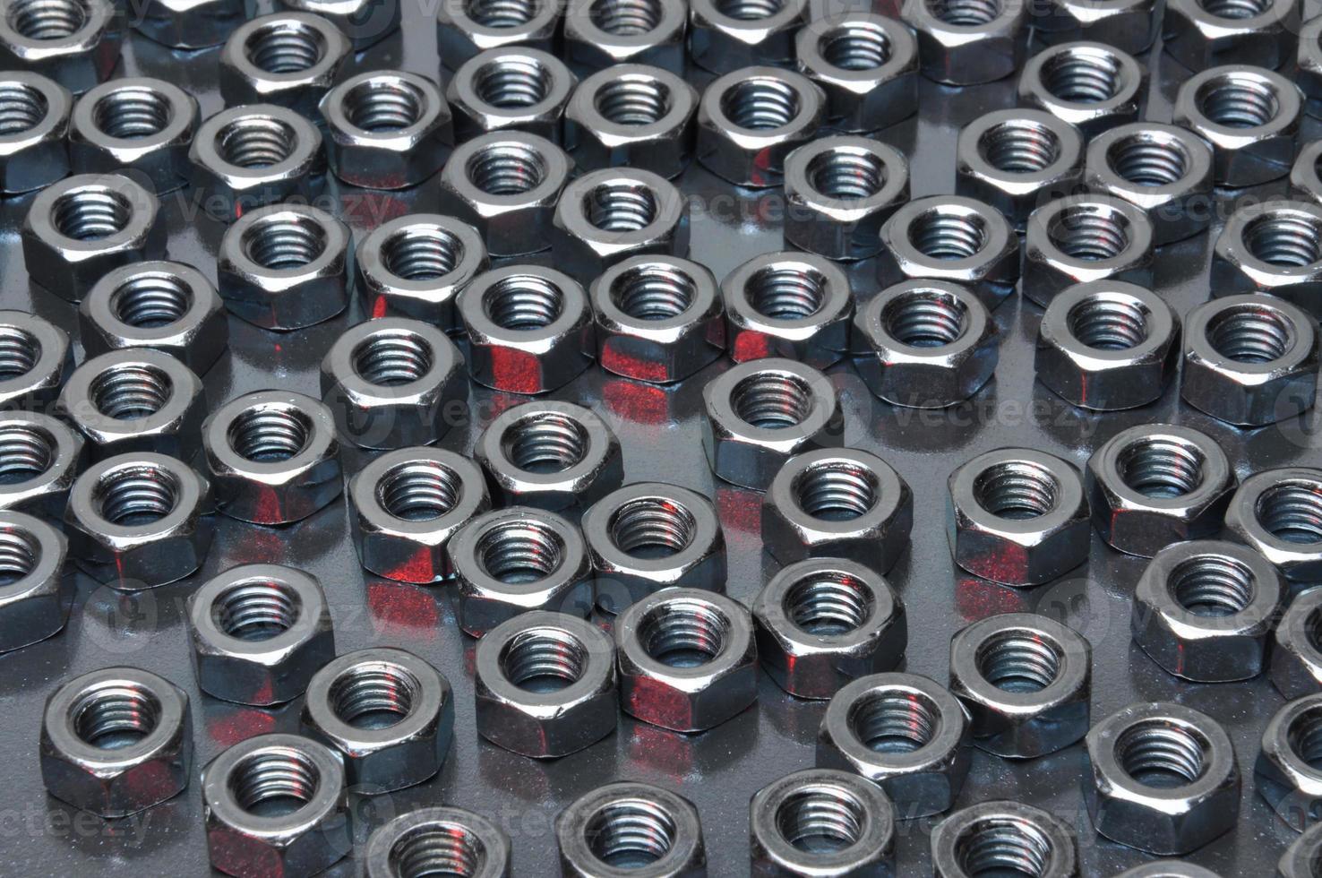 tuercas metálicas brillantes sobre una superficie metálica foto