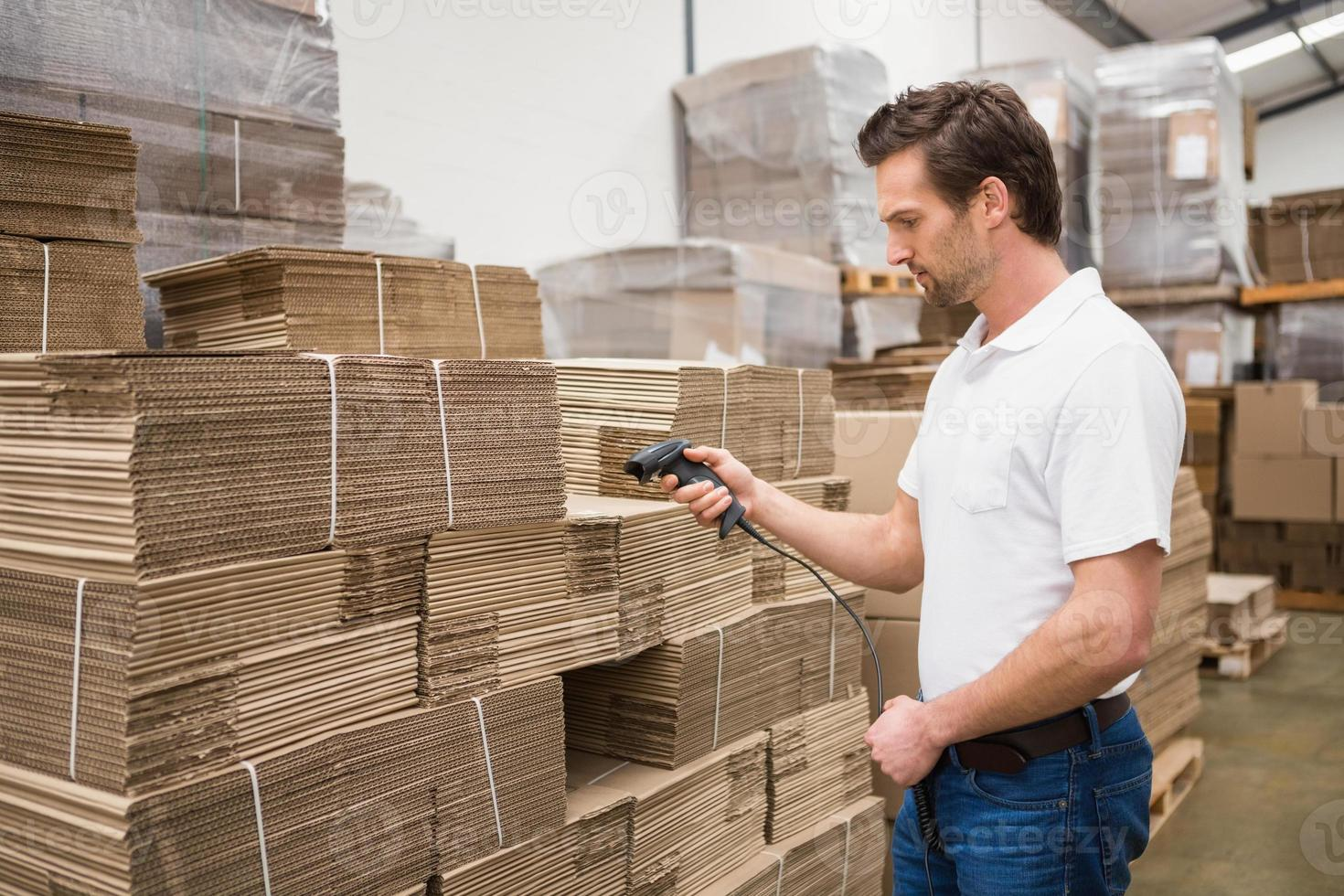 Serious warehouse worker holding scanner photo
