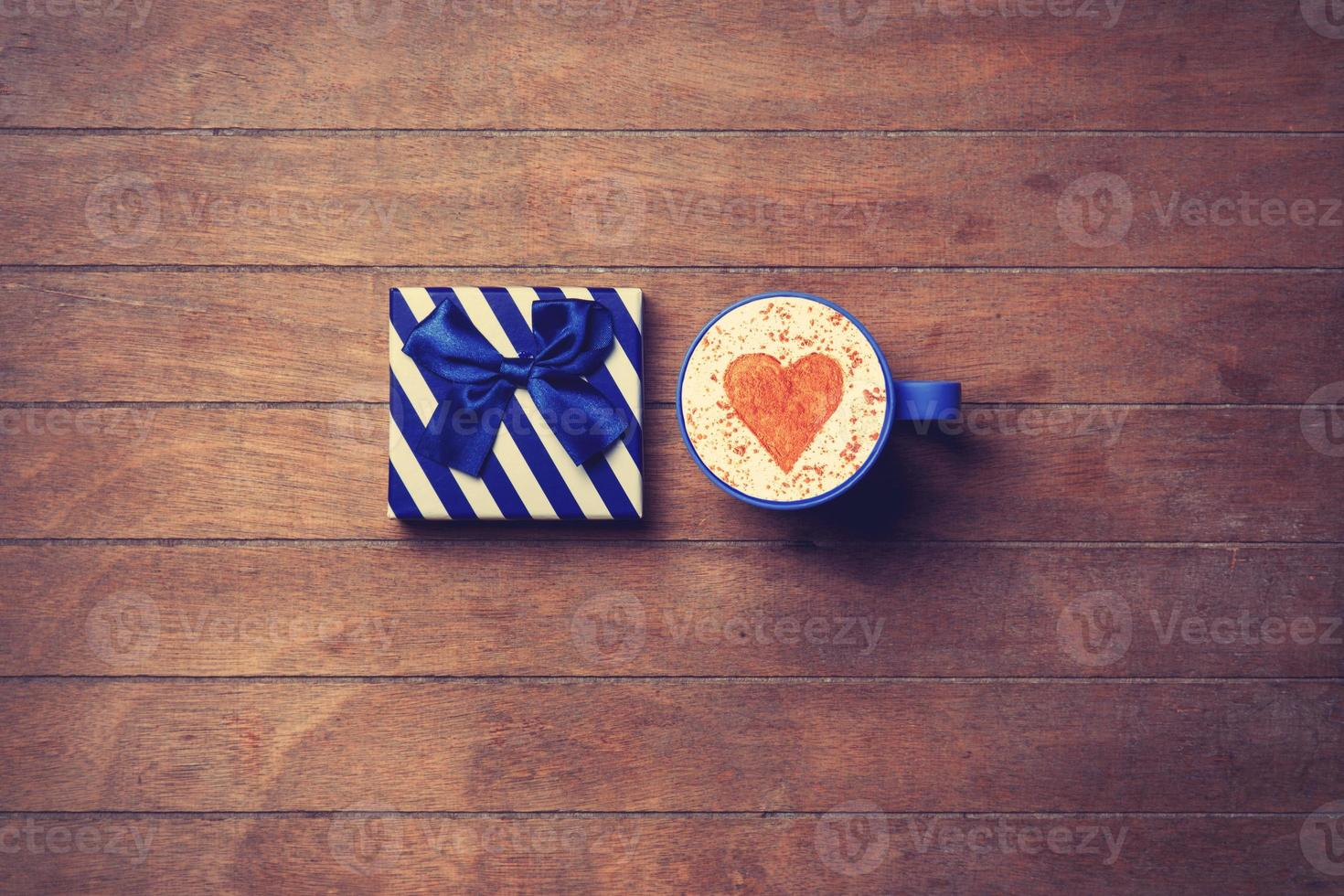 Cup and gift box on wooden background photo