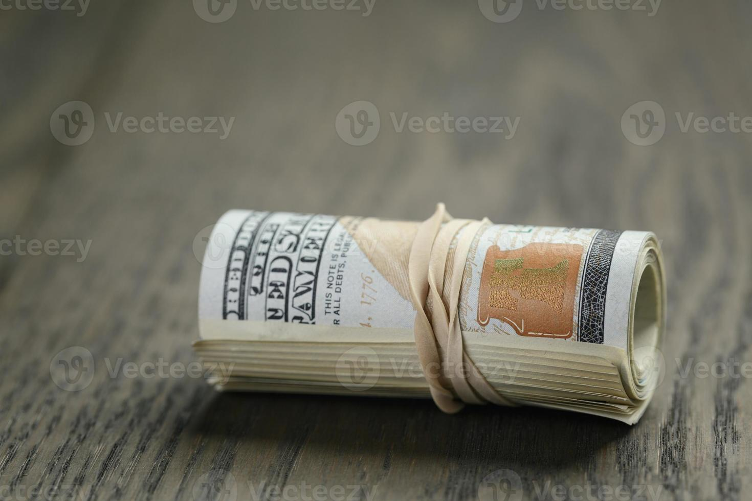 roll of hundred dollar bills on wooden table photo