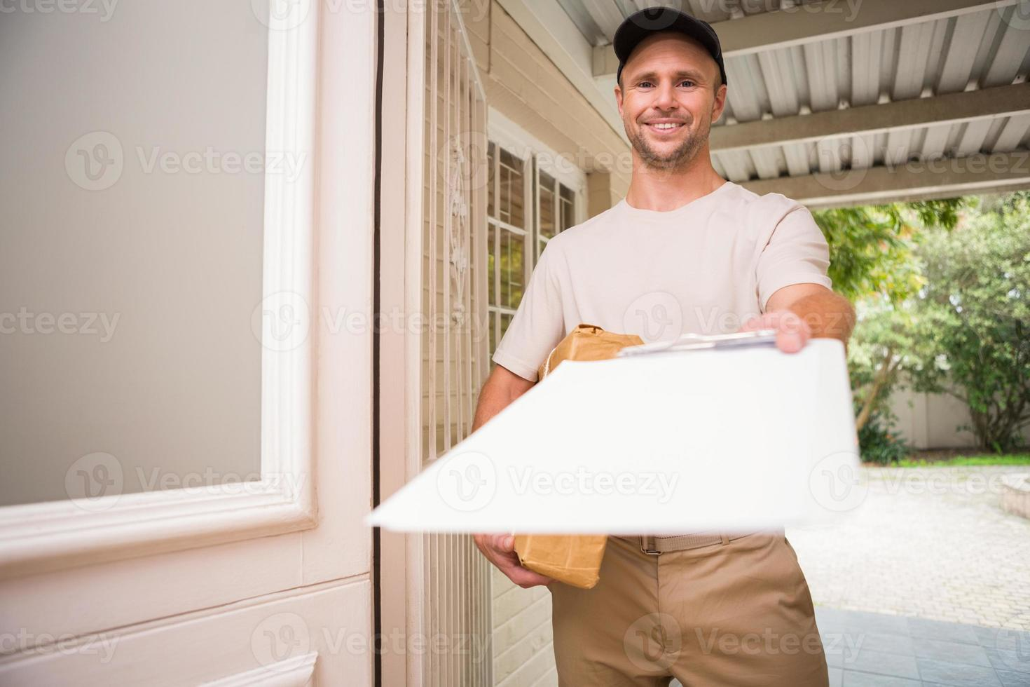Happy delivery man showing clipboard photo