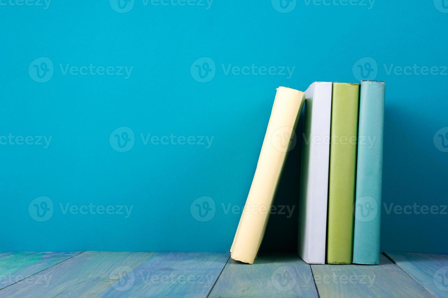 Row of books, grungy blue background, free copy space photo