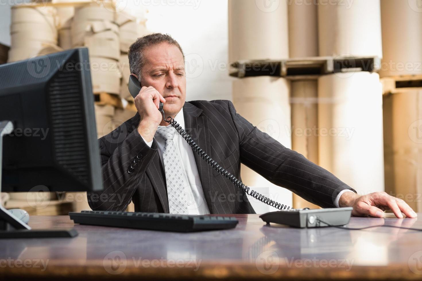 Warehouse manager using telephone and laptop photo
