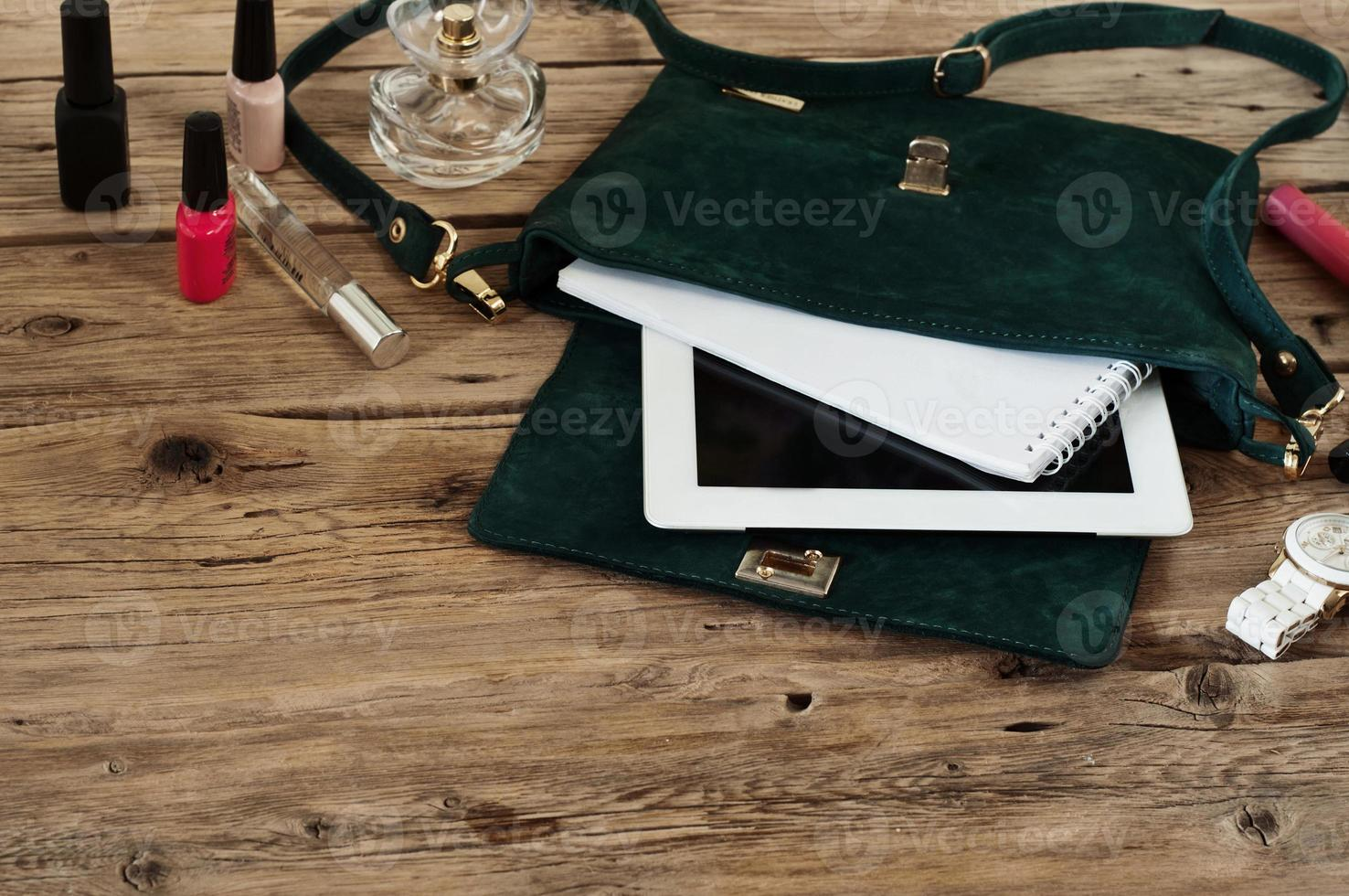 Suede female bag with tablet, notepads, white watch and cosmetic photo