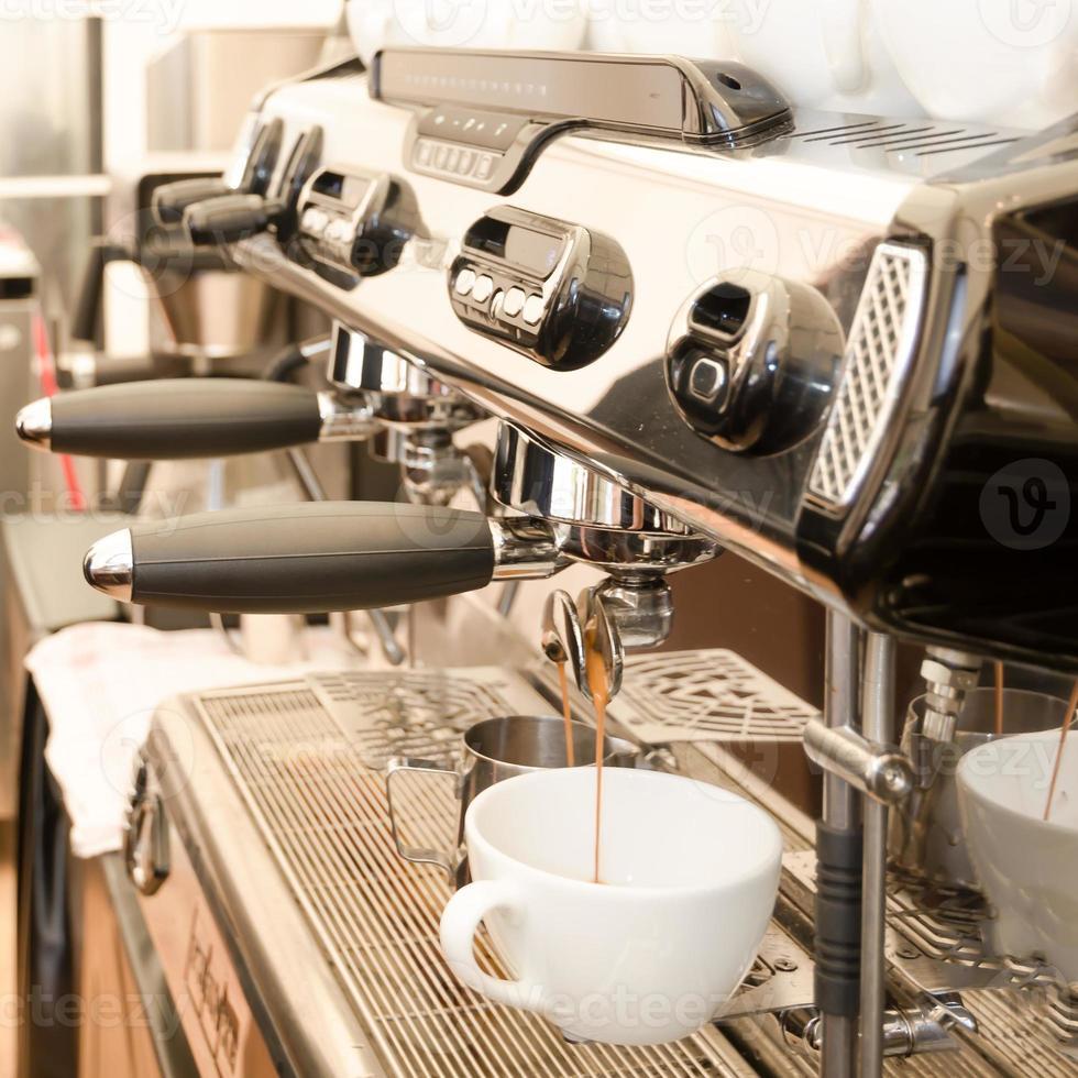 Large espresso machine in a coffee shop with a white mug photo