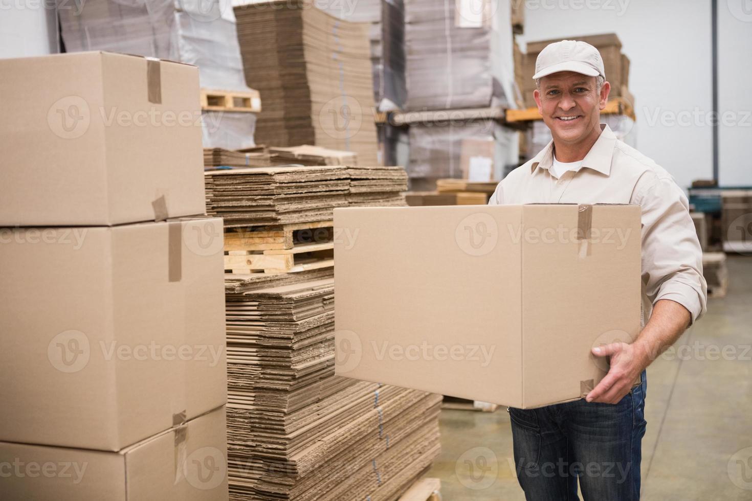 Retrato de trabajador llevando caja foto