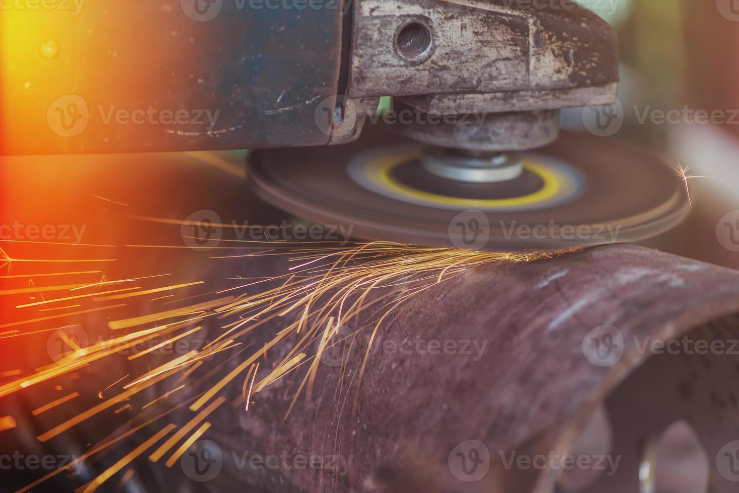 Worker grinding steel pipe with grinder photo