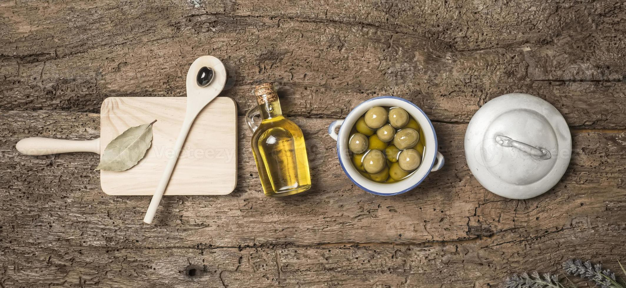 OLive oil and olives wooden table photo